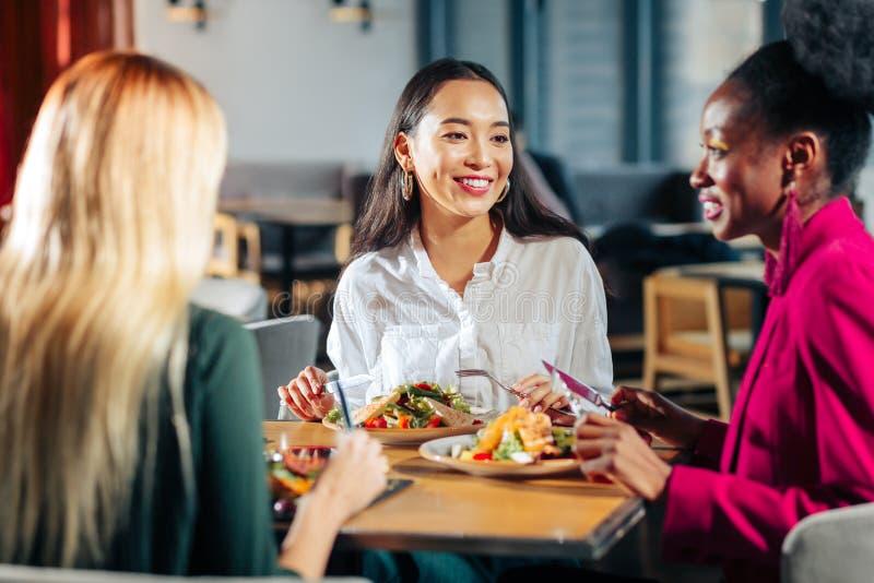 Τρεις φίλοι που τρώνε τις εύγευστες σαλάτες στο αγαπημένο εστιατόριό τους στοκ εικόνα