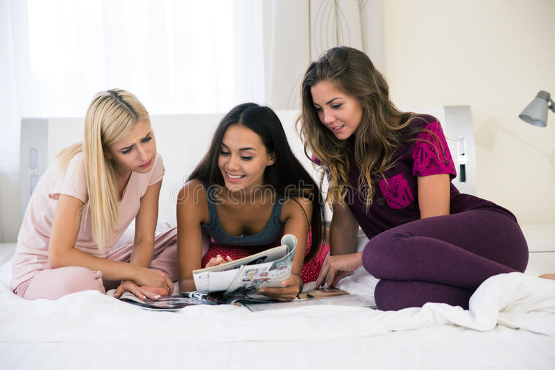 Τρεις φίλες που διαβάζουν το περιοδικό στο κρεβάτι στοκ φωτογραφία
