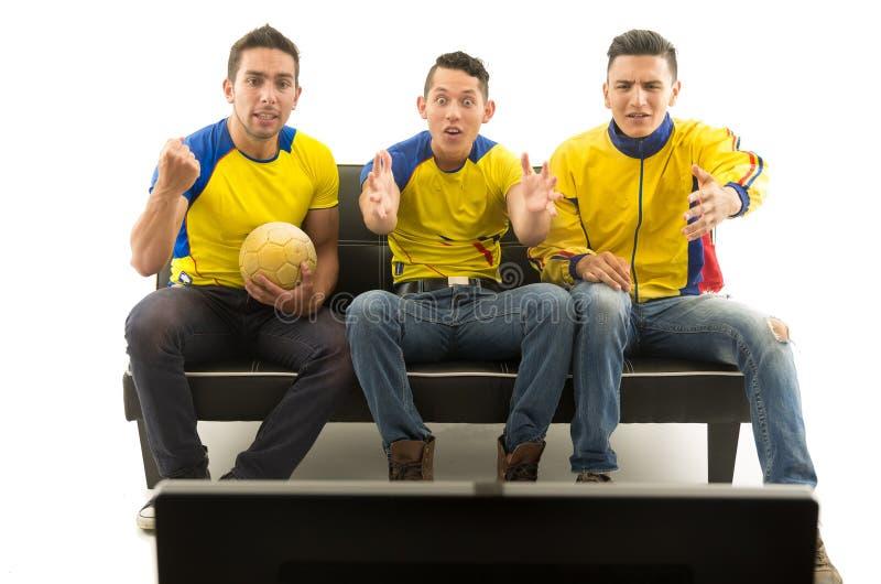 Τρεις φίλοι που κάθονται στον καναπέ που φορά τα κίτρινα αθλητικά πουκάμισα που προσέχουν την τηλεόραση με τον ενθουσιασμό, άσπρο στοκ εικόνα