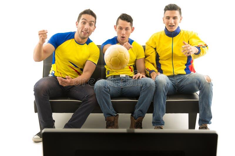 Τρεις φίλοι που κάθονται στον καναπέ που φορά τα κίτρινα αθλητικά πουκάμισα που προσέχουν την τηλεόραση με τον ενθουσιασμό, χρυσή στοκ φωτογραφία