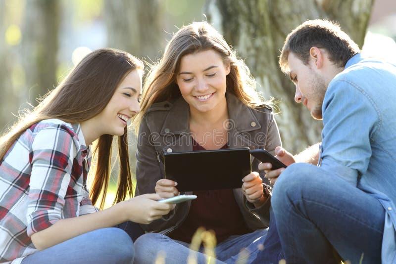 Τρεις φίλοι που χρησιμοποιούν τις πολλαπλάσιες συσκευές υπαίθρια στοκ φωτογραφία με δικαίωμα ελεύθερης χρήσης