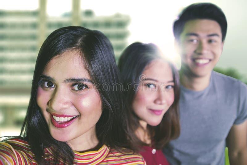 Τρεις φοιτητές πανεπιστημίου που παίρνουν μια φωτογραφία από κοινού στοκ φωτογραφίες με δικαίωμα ελεύθερης χρήσης