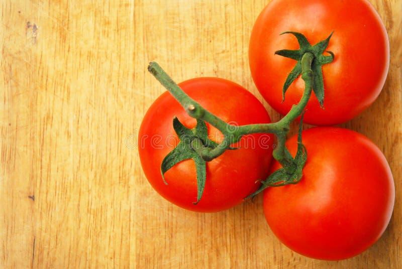 Τρεις φρέσκες ντομάτες είναι κόκκινο και πράσινο τερματικό φρούτων στοκ φωτογραφίες με δικαίωμα ελεύθερης χρήσης