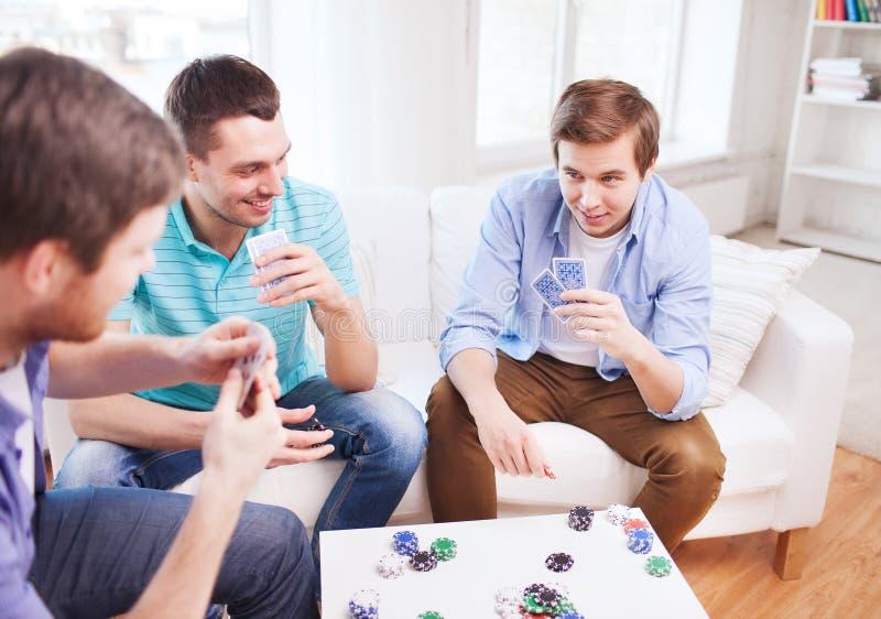 Τρεις χαμογελώντας αρσενικοί φίλοι που παίζουν τις κάρτες στο σπίτι στοκ εικόνα