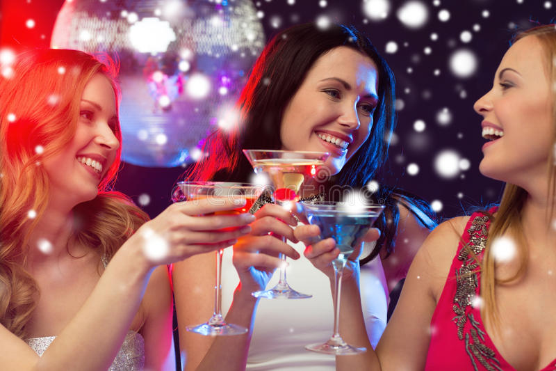 Τρεις χαμογελώντας γυναίκες με τα κοκτέιλ και τη σφαίρα disco στοκ φωτογραφία