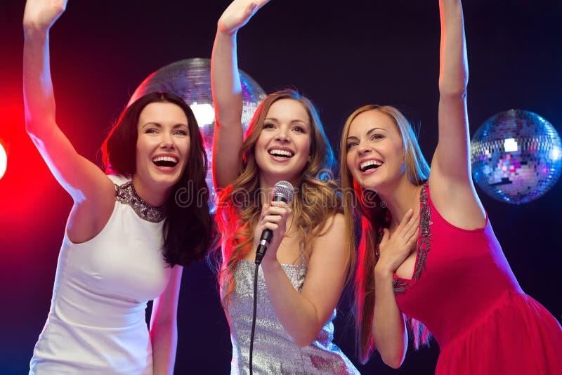Τρεις χαμογελώντας γυναίκες που χορεύουν και που τραγουδούν το καραόκε στοκ εικόνα με δικαίωμα ελεύθερης χρήσης