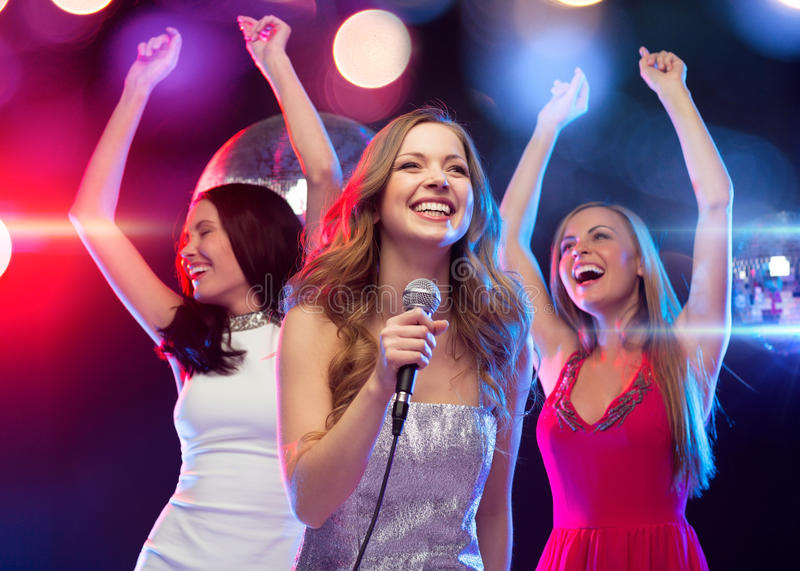 Τρεις χαμογελώντας γυναίκες που χορεύουν και που τραγουδούν το καραόκε στοκ φωτογραφία με δικαίωμα ελεύθερης χρήσης