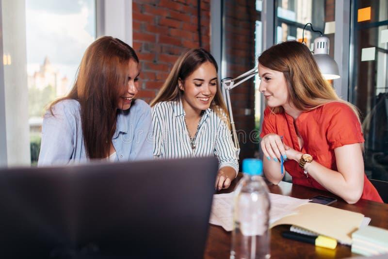 Τρεις χαμογελώντας θηλυκοί φοιτητές πανεπιστημίου που εργάζονται στο πρόγραμμα μαζί στην τάξη στοκ εικόνες