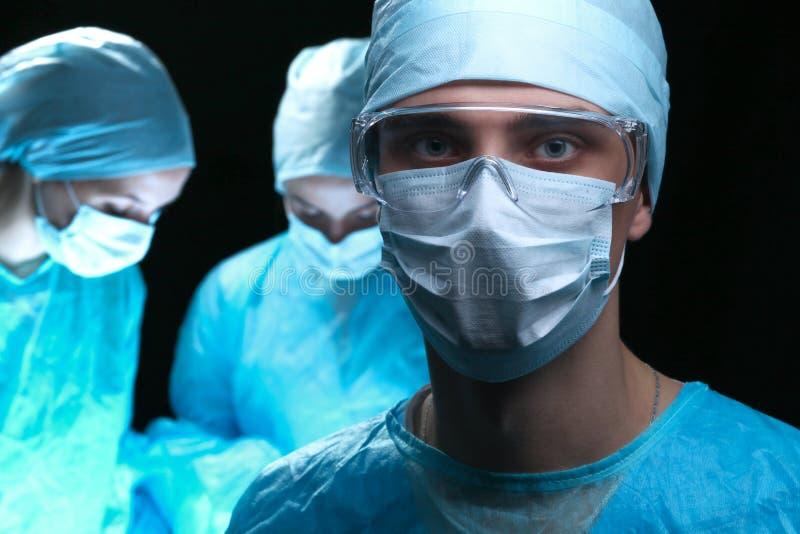 Τρεις χειρούργοι στην εργασία που λειτουργεί στο χειρουργικό ασθενή αποταμίευσης θεάτρων και που εξετάζει το όργανο ελέγχου ζωής  στοκ εικόνα με δικαίωμα ελεύθερης χρήσης