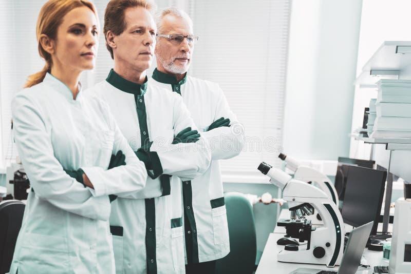 Τρεις χημικοί ερευνητές που στέκονται κοντά στο σύγχρονο μικροσκόπιο στοκ φωτογραφίες με δικαίωμα ελεύθερης χρήσης