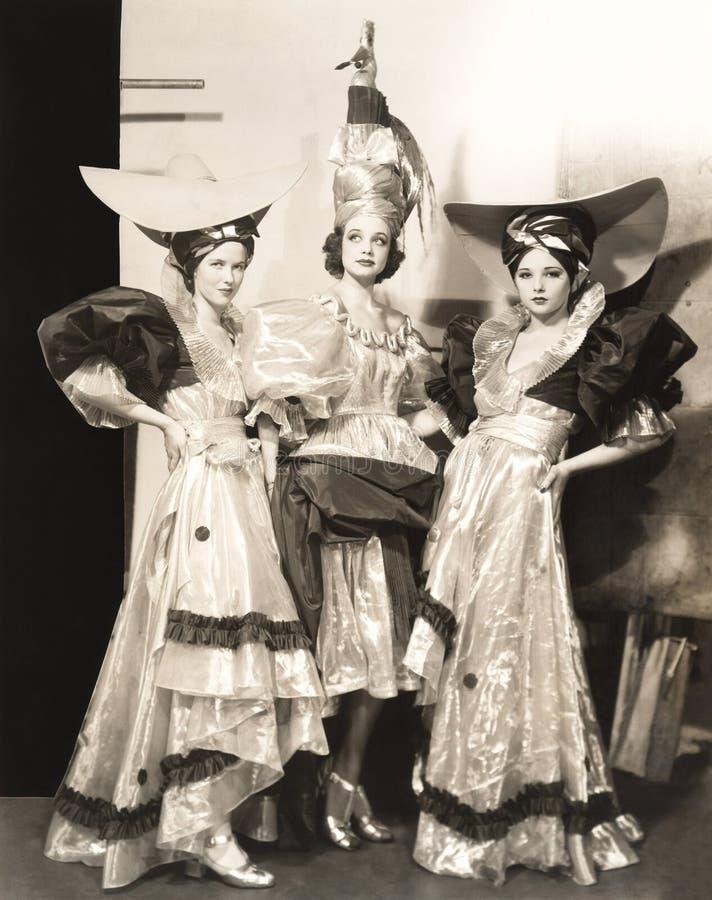Τρεις χορευτές στα μακριά φορέματα και τα μεγάλα καπέλα στοκ εικόνες με δικαίωμα ελεύθερης χρήσης
