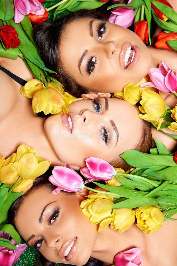 Τρεις όμορφες αισθησιακές γυναίκες με τις ζωηρόχρωμες τουλίπες στοκ εικόνα