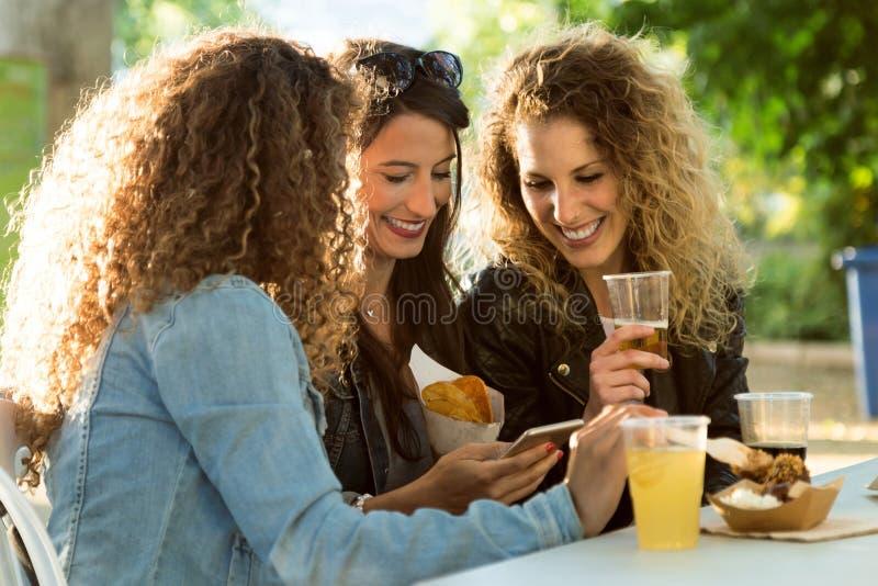 Τρεις όμορφες νέες γυναίκες που χρησιμοποιούν αυτοί κινητό τηλέφωνο στην οδό στοκ φωτογραφία