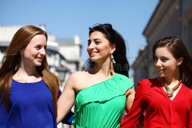 Τρεις όμορφες νέες γυναίκες στο ζωηρόχρωμο φόρεμα στοκ φωτογραφίες