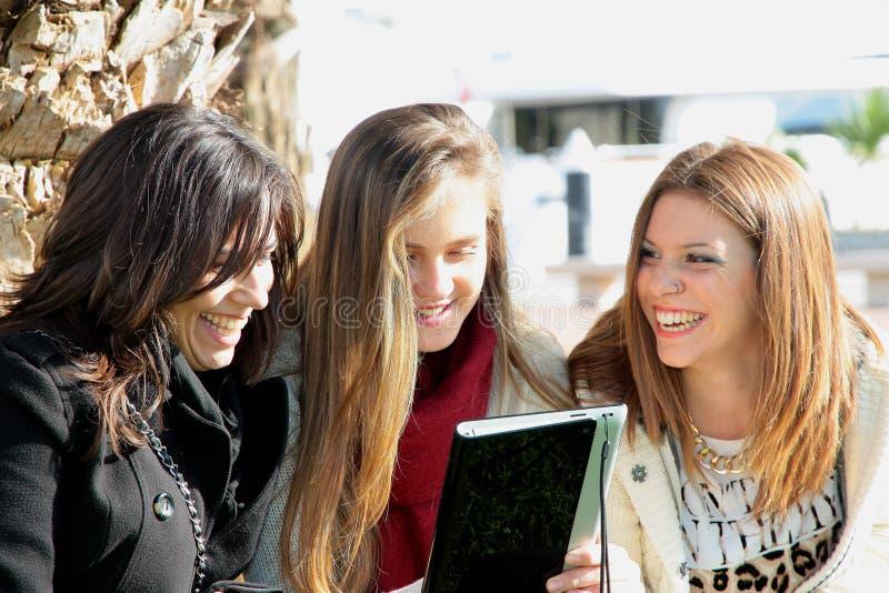 Τρεις όμορφοι φίλοι που απολαμβάνουν με μια ταμπλέτα. στοκ εικόνα με δικαίωμα ελεύθερης χρήσης