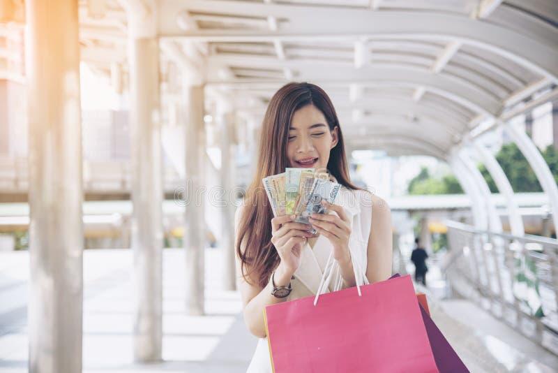 Τρελλές shopaholic τσάντες αγορών εκμετάλλευσης γυναικών, χρήματα, πρόσωπο πιστωτικών καρτών στις λεωφόρους αγορών Μοντέρνος σε α στοκ φωτογραφίες