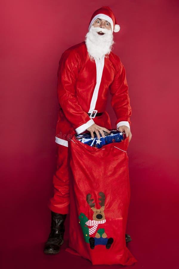 Τρελλός Άγιος Βασίλης παρουσιάζει δώρα σε μια τσάντα στοκ φωτογραφία με δικαίωμα ελεύθερης χρήσης