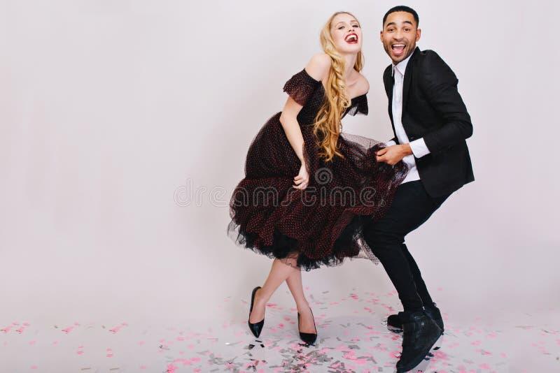 Τρελλός αστείος εορτασμός του χαρούμενου ζεύγους ερωτευμένος στα ενδύματα βραδιού πολυτέλειας που έχουν τη διασκέδαση μαζί στο άσ στοκ φωτογραφία