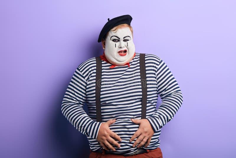 Τρελλός αστείος παχουλός κλόουν που έχει ένα πρόβλημα με το στομάχι του στοκ φωτογραφία με δικαίωμα ελεύθερης χρήσης