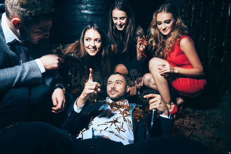 τρελλό συμβαλλόμενο μέρ&omicr Μεθυσμένο άτομο που βρίσκεται στο πάτωμα στοκ φωτογραφίες