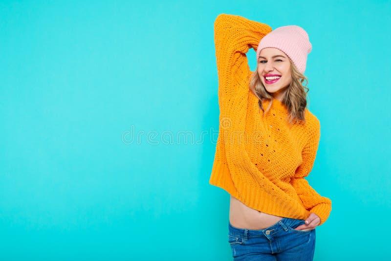 Τρελλό όμορφο καθιερώνον τη μόδα κορίτσι με το αναιδές χαμόγελο στα ζωηρόχρωμα ενδύματα και το ρόδινο καπέλο beanie Ελκυστικό δρο στοκ φωτογραφίες