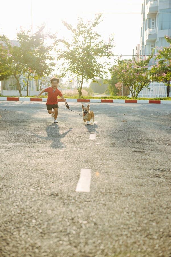 Τρεξίματα αγοριών παιδιών στην οδό με το σκυλί κατοικίδιων ζώων του στοκ φωτογραφία