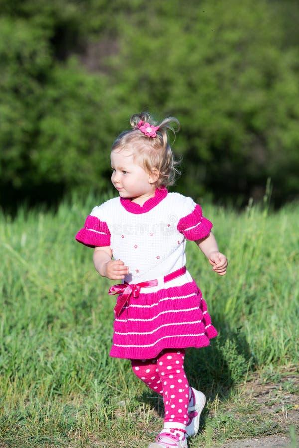 Τρεξίματα κοριτσιών παιδιών Llittle στη χλόη στο λιβάδι στοκ εικόνα