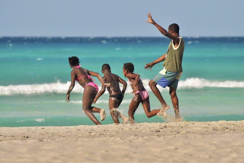 Τρεξίματα μπαμπάδων με τα ευτυχή παιδιά στην ακτή στοκ φωτογραφίες
