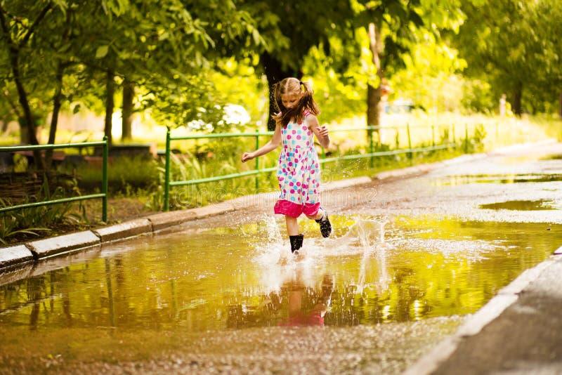 Τρεξίματα παιδάκι μέσω μιας λακκούβας καλοκαίρι υπαίθριο στοκ εικόνες