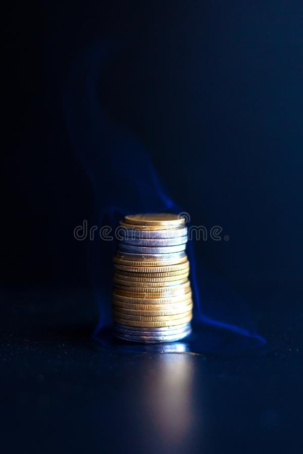 Τρεξίματα χρημάτων έννοιας έξω γρήγορα, έγκαυμα νομισμάτων μετάλλων με μια μπλε φλόγα στοκ φωτογραφία με δικαίωμα ελεύθερης χρήσης