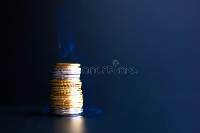 Τρεξίματα χρημάτων έννοιας έξω γρήγορα, έγκαυμα νομισμάτων μετάλλων με μια μπλε φλόγα στοκ εικόνα με δικαίωμα ελεύθερης χρήσης