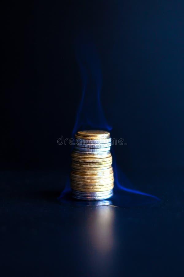 Τρεξίματα χρημάτων έννοιας έξω γρήγορα, έγκαυμα νομισμάτων μετάλλων με μια μπλε φλόγα στοκ εικόνες με δικαίωμα ελεύθερης χρήσης