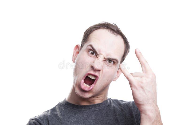 Τρελλός ο νεαρός άνδρας φωνάζει και παρουσιάζει βράχο - και - σημάδι χεριών ρόλων στοκ φωτογραφία με δικαίωμα ελεύθερης χρήσης