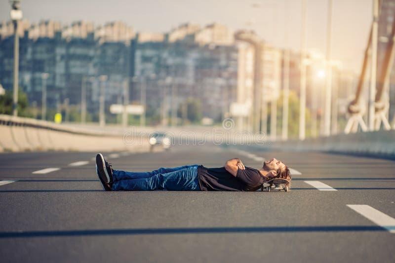 Τρελλό skateboarder που ξαπλώνει στη μέση μιας γέφυρας εθνικών οδών στοκ φωτογραφία