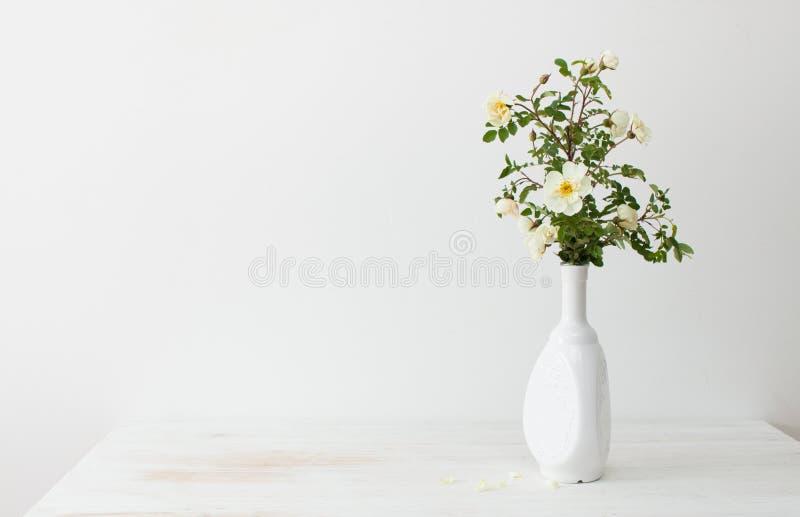 Τριαντάφυλλα κήπων σε ένα άσπρο βάζο σε έναν πίνακα στοκ φωτογραφία με δικαίωμα ελεύθερης χρήσης