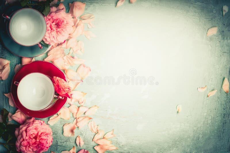 Τριαντάφυλλα με τα πέταλα και φλυτζάνια στο τυρκουάζ υπόβαθρο, τοπ τσάι γυναικείων προγευμάτων πρωινού άποψης στοκ φωτογραφία