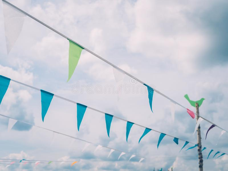 Τριγωνικές σημαίες στο σχοινί ενάντια στα σύννεφα κατά τη διάρκεια του θερινού φεστιβάλ στοκ εικόνες