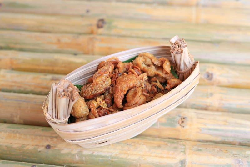Τριζάτα τηγανισμένα δέρματα κοτόπουλου που εξυπηρετούνται στο ξηρό κύπελλο φύλλων στοκ εικόνες