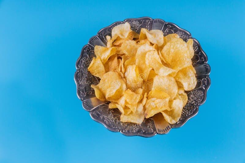 Τριζάτα τσιπ πατατών σε ένα ασημένιο κύπελλο στο μπλε υπόβαθρο στοκ φωτογραφίες με δικαίωμα ελεύθερης χρήσης
