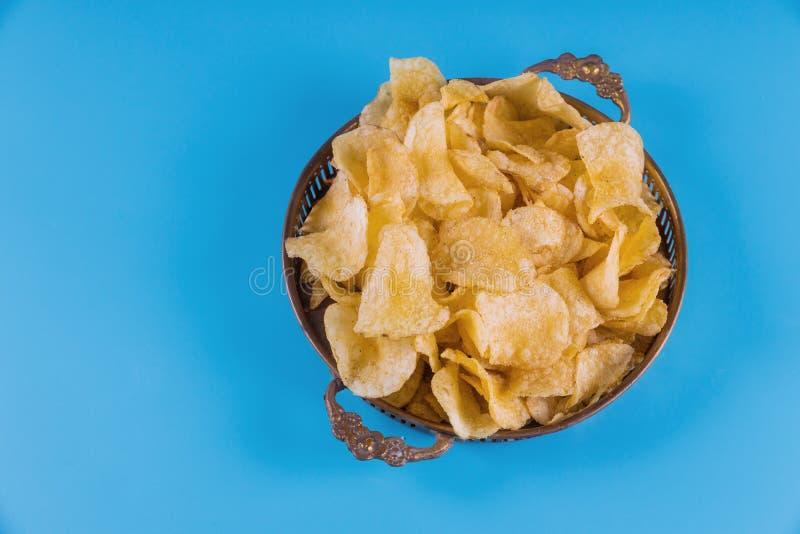 Τριζάτα τσιπ πατατών στο ασημένιο κύπελλο στο μπλε υπόβαθρο στοκ φωτογραφία με δικαίωμα ελεύθερης χρήσης