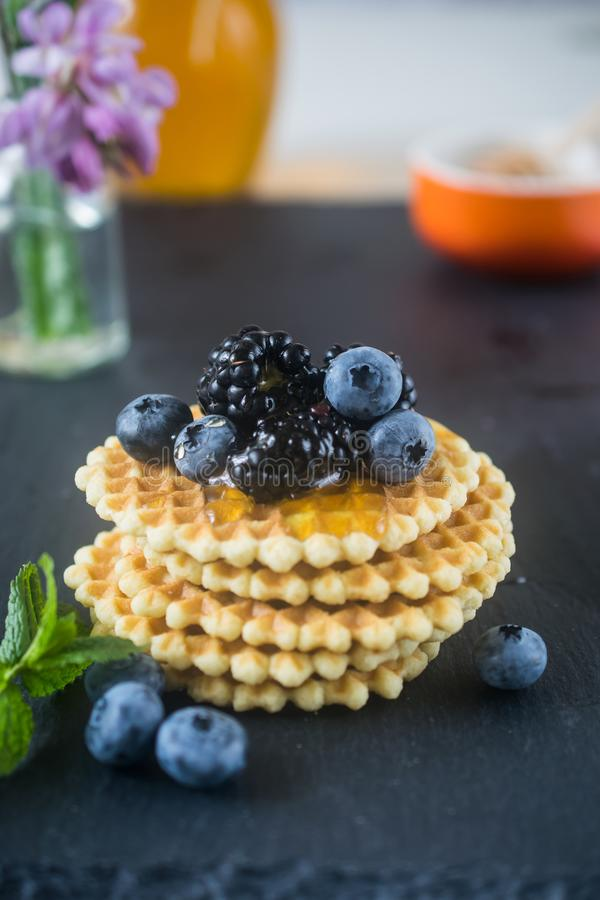 Τριζάτες σπιτικές στρογγυλές βελγικές βάφλες με τα μούρα και μέλι στην κορυφή στοκ εικόνα
