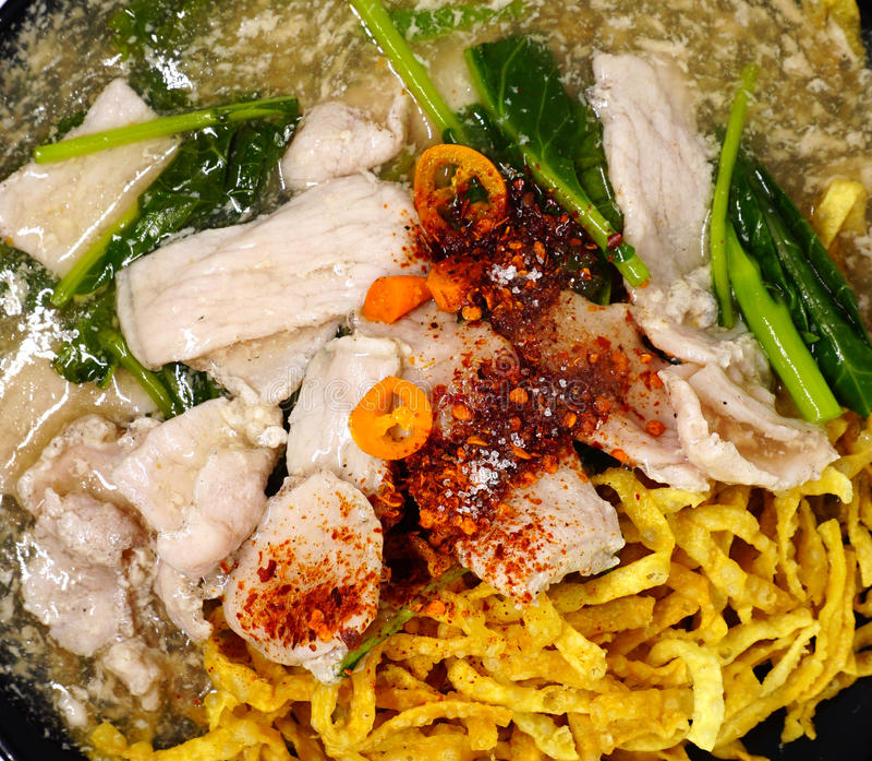 Τριζάτο τηγανισμένο χοιρινό κρέας νουντλς με τη σάλτσα raadna και κορυφή με τα ταϊλανδικά τσίλι στοκ εικόνες με δικαίωμα ελεύθερης χρήσης
