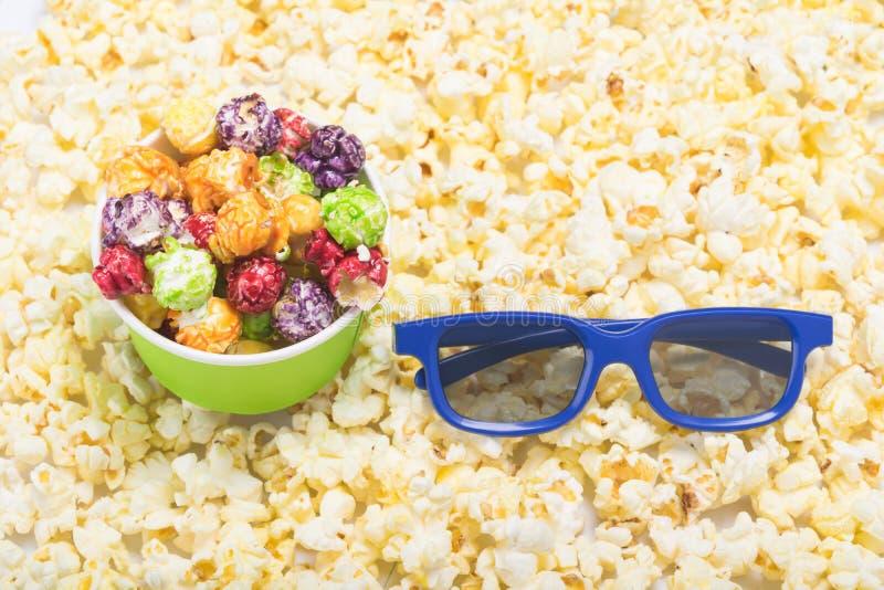 τρισδιάστατα γυαλιά και φλυτζάνι εγγράφου με πολύχρωμο popcorn στο υπόβαθρο των διεσπαρμένων έτοιμων πυρήνων καλαμποκιού στοκ εικόνα με δικαίωμα ελεύθερης χρήσης