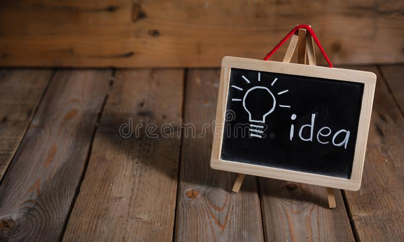 τρισδιάστατη εικόνα ιδέας έννοιας που δίνεται Λάμπα φωτός που επισύρεται την προσοχή σε έναν πίνακα κιμωλίας, σκοτεινό ξύλινο υπό στοκ φωτογραφίες
