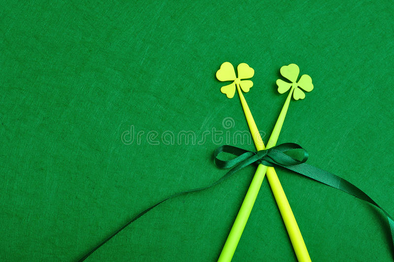 Τριφύλλια τέσσερα φύλλων ραβδιά έδεσαν μαζί με ένα πράσινο τόξο στοκ εικόνες με δικαίωμα ελεύθερης χρήσης