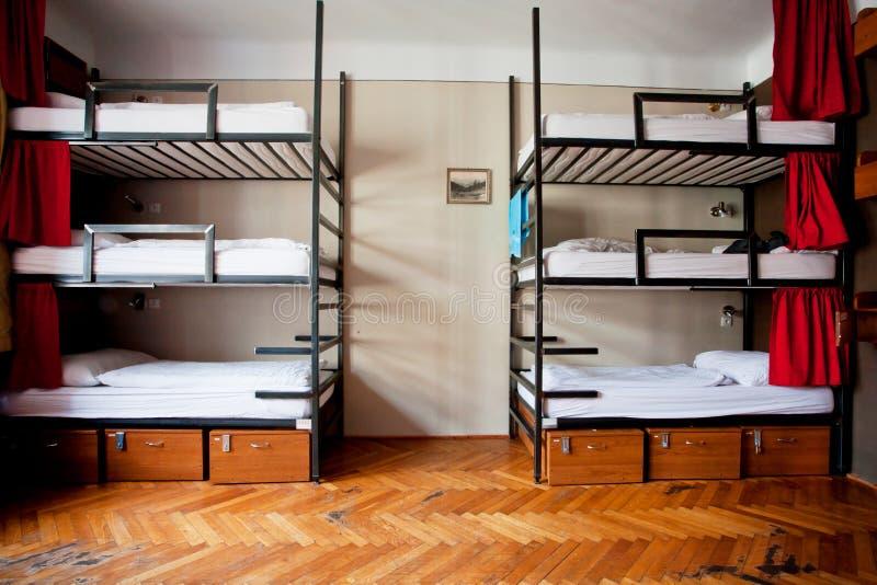 Τριών επιπέδων κρεβάτια κοιτώνων μέσα στο δωμάτιο ξενώνων για έξι στοκ φωτογραφία