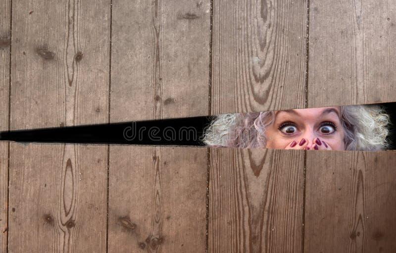 Τρομαγμένη γυναίκα που τιτιβίζει μέσω ενός χάσματος στοκ φωτογραφίες