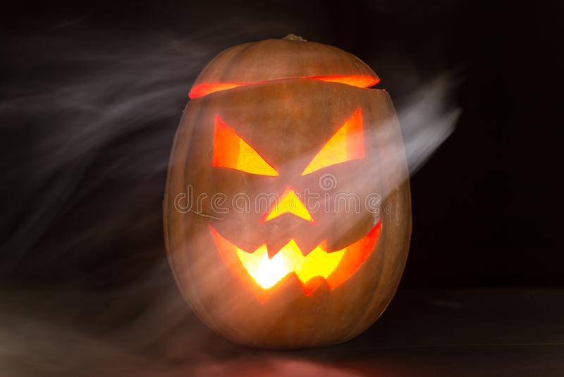 Τρομακτικά Jack-ο-φανάρια κολοκύθας αποκριών με ένα σημάδι που απομονώνεται στο Μαύρο στοκ φωτογραφία