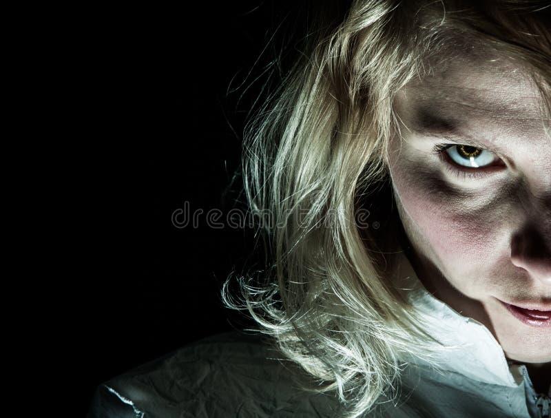 Τρομακτική ξανθή γυναίκα που εξετάζει τη κάμερα στοκ εικόνες
