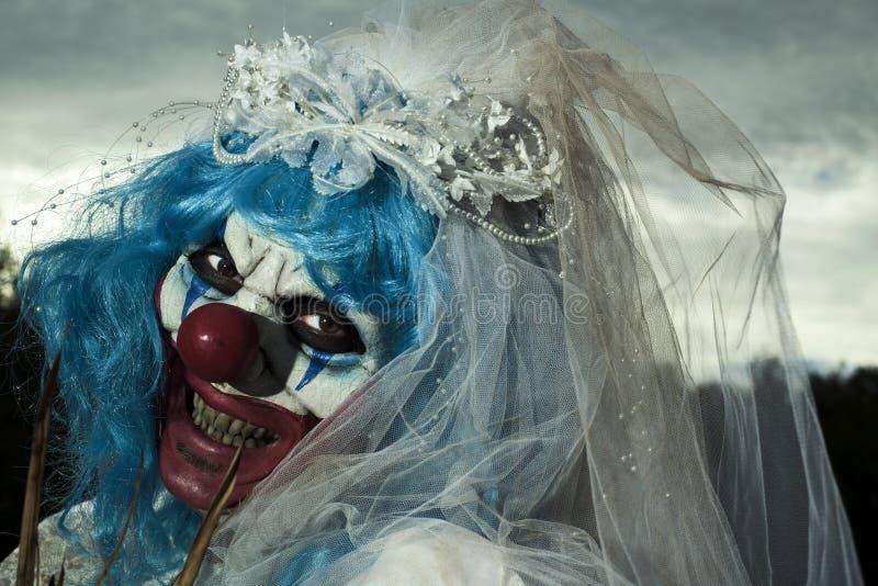 Τρομακτικός κακός κλόουν σε ένα φόρεμα νυφών στοκ εικόνα